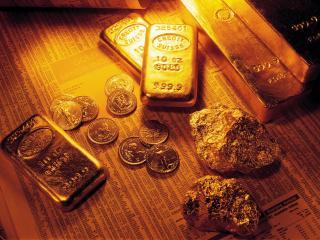 обои Золотые слитки, самородки и монеты на биржевых сводках фото