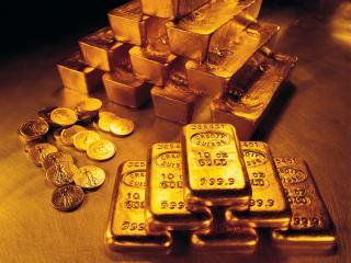 обои Две пирамиды золотых слитков и куча монет фото