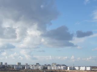 обои Голубое небо с облаками и город на горизонте фото