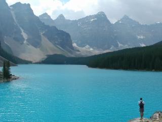 обои Человек любуется на голубое озеро в горах фото