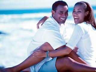 обои Влюблённые сидят на берегу моря фото
