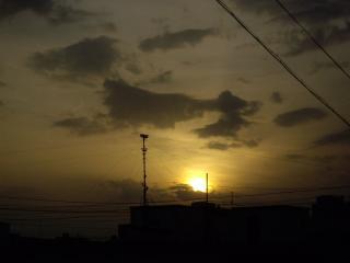 обои Солнце опускается за крышу дома фото