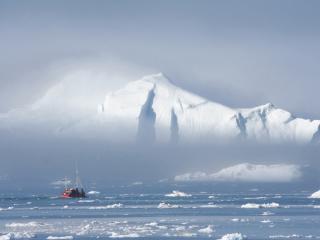 обои Рыбацкая лодка у края большого айсберга фото