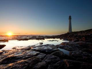 обои Маяк на каменистом побережье. Закат солнца фото