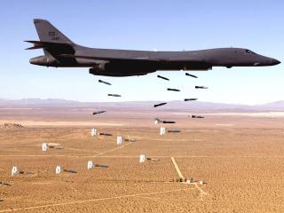 обои Самолет сбрасывающий бомбы над полем фото