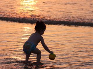 обои Девочка в памперсе играется на берегу фото