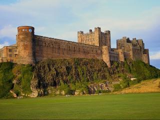 обои Огромная каменная крепость на зеленом взгорье фото