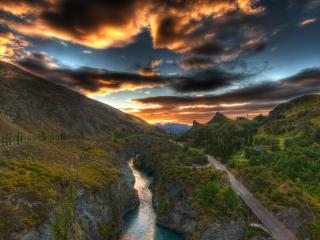 обои Дорога вдоль реки,   под грозовым закатным небом фото