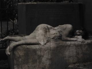 обои Обессилевшая девушка лежит на каменной плите фото