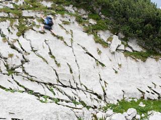 обои Альпинист взбирается по отвесной стене горы фото