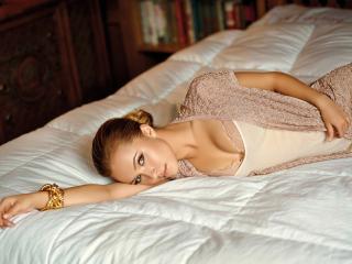 обои Девушка лежит на белой постели фото