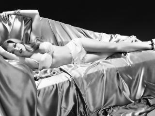 обои Девушка на диване покрытым атласным шелком фото