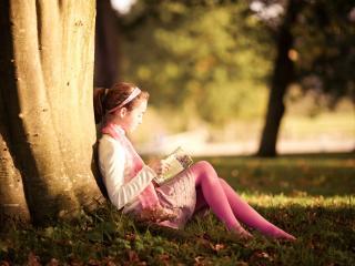 обои Девочка с книгой в парке под деревом фото