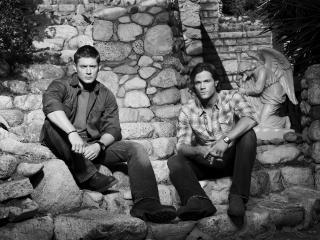 обои Два мужчины возле каменной стены фото