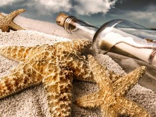 обои Бутылка с запиской и морские звездочки на пляже фото