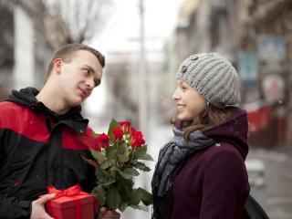 обои Парень дарит своей девушке букет роз и подарок фото