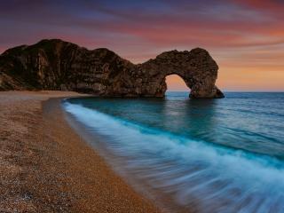 обои Скала выходящая из моря на вечернем закате фото