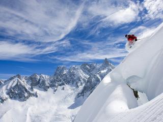 обои Горнолыжник на вираже скалистых заснеженных гор фото