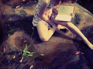 обои Девушка на камне сидит и читает фото