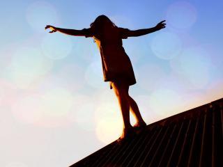 обои Девушка на крыше дома при закате фото
