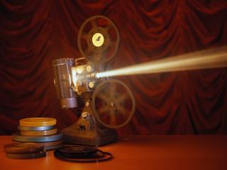 обои Кинопроектор с фильмами на столе фото
