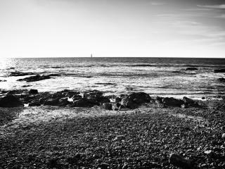 обои Каменистый берег моря,   маяк вдали фото