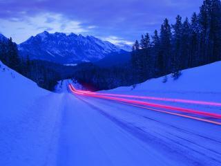 обои Снежная дорога в горах вдоль леса,   поздний вечер фото
