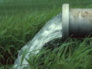 обои Поток воды из трубы на зеленую траву фото
