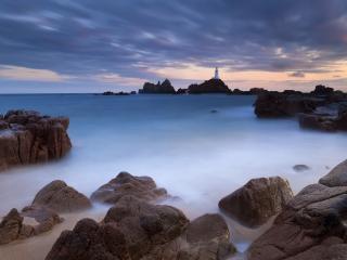 обои Морские камни и маяк вдали фото