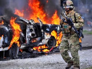 обои Солдат в экиперовке у горящего авто фото