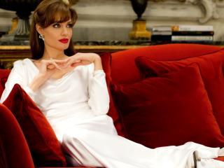 обои Джоли на красном диване с подушками фото