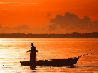 обои Рыбак на лодке с сетями фото