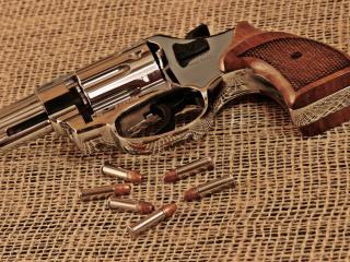 обои Красивый маленький револьвер и пули на мешковине фото