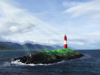 обои Одинокий маяк на маленьком островке каменистом фото