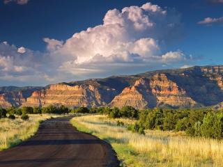 обои Извилистая дорога и облака над горами