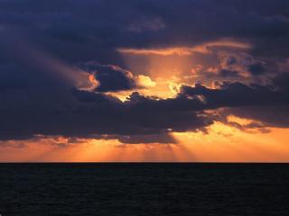 обои Багряное солнце заходящее в свинцовых облаках фото