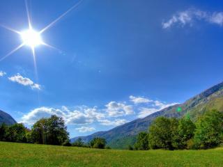 обои Солнце в зените над горной долиной фото