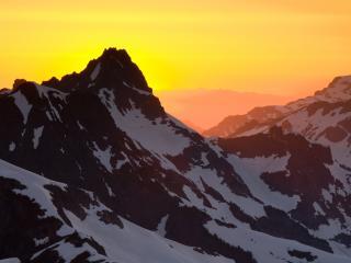 обои Каменные вершины со снегом на фоне желтого заката