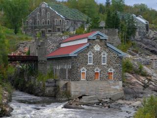 обои Строения на породе скальной у небольшой реки фото