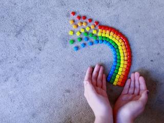 обои Руки с кусочком радуги из конфет фото