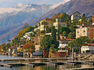 обои Небольшой городок с пирсами у моря в подножьи гор фото