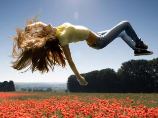 обои Девушка парит в мечтах над маковым полем фото