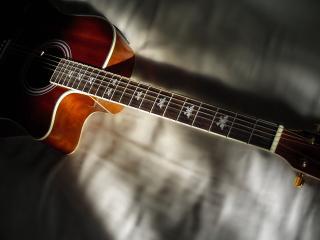 обои Красивая гитара лежит на постели фото
