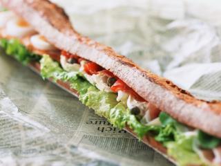 обои Длинный бутерброд лежит на газете фото