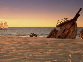 обои Разбитое судно у берега и парусник на горизонте фото