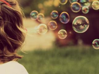 обои Девочка пускает мыльные пузырьки фото