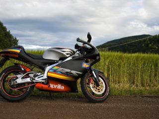 обои Мотоцикл на обочине у зеленого поля фото