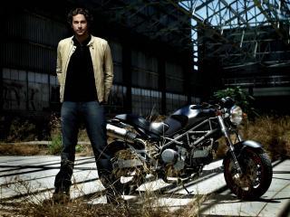 обои Красивый мужчина у мотоцикла стоит фото