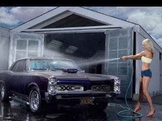 обои У автомойки моет  девушка машину со шланга фото