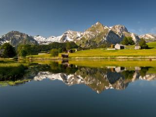 обои Небольшое озеро на деревне в горах фото